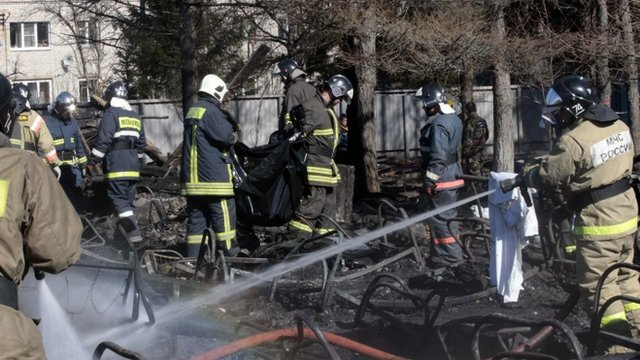 Russian emergency service staff spray water and remove remains at the site of a fire at a psychiatric hospital in the village of Ramensky