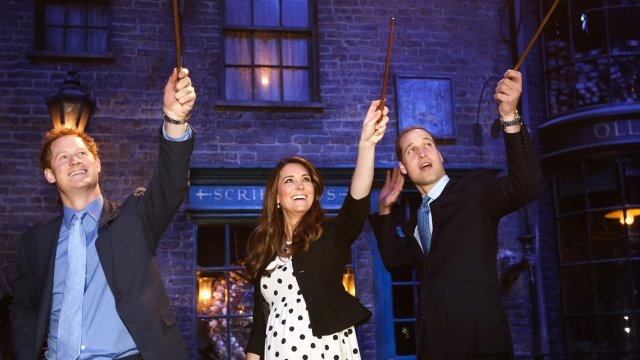 Prince Harry and the Duke and Duchess of Cambridge waving wands on Diagon Alley