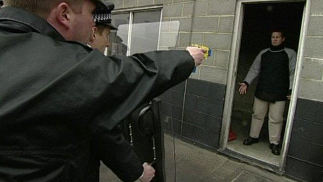 Police officer aims Taser at man