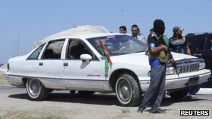 Masked gunman stands next to a vehicle in which three army personnel were killed in Ramadi (27 April 2013)