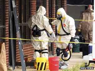 Officials wearing hazmat suits search a martial arts studio previously run by Everett Dutschke in Tupelo (24 April 2013)