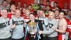 Cliftonville players and staff celebrate in the dressing room after picking up the Gibson Cup at Solitude