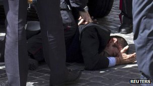 A man believed to be the gunman is detained outside the Chigi palace, Rome, 28 April