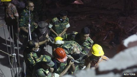 A rescuer injured in the fire is taken from the scene in Savar, Dhaka, Bangladesh