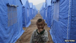 A child stands next to tents that serve as dwellings for local residents after the 20 April earthquake, in Longmen township of Lushan county, Sichuan province, 27 April 2013