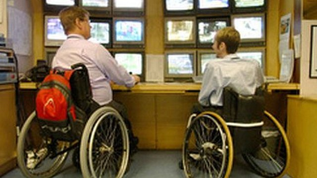 Two wheel-chair users at work