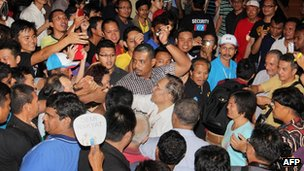 This picture taken on 26 April 2013 shows Malaysia's opposition leader Anwar Ibrahim (centre) being greeted by his supporters during a campaign event on the island of Borneo