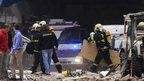 Policemen and firefighters inspect the scene of an explosion in downtown Prague