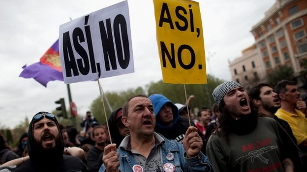 "Spanish protestors with signs reading ""not this way"""