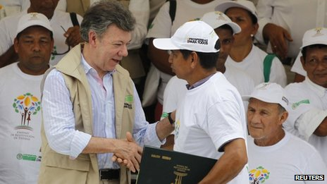 Juan Manuel Santos hands a land title to a displaced person on 10 April 2013