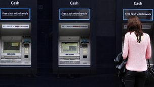 A woman uses one of a line of cash dispensers in central London