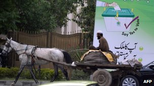 A horse-driven cart passes by an electoral billboard in Islamabad