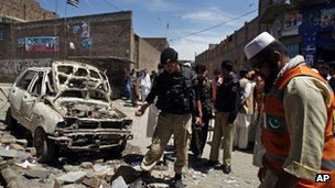 Pakistani police officers and volunteers visit the site of an explosion in Peshawar, Pakistan