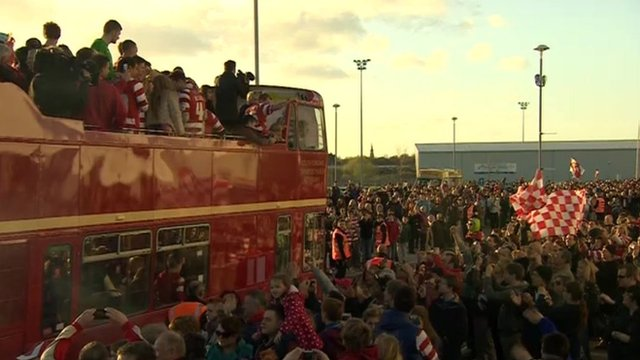 Fans cheer as open top bus travels past them