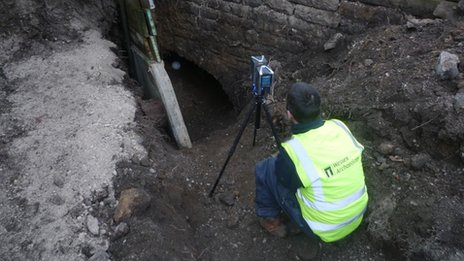 An archaeologist at the entrance of the tunnel uses a laser scanner