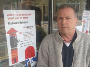 Businessman Tom Murray next to a poster opposing residents' parking in Bishopston