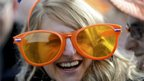 Woman wearing large orange glasses at the Royal Palace in Amsterdam (30 April 2013)