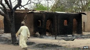 A man walks past burnt houses in the remote north-eastern town of Baga in Nigeria on 21 April 2013 after clashes