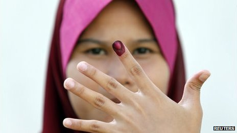 A Malaysian voter shows her ink-stained finger after casting her ballot during the early voting for the general elections in Kuala Lumpur, 30 April 2013