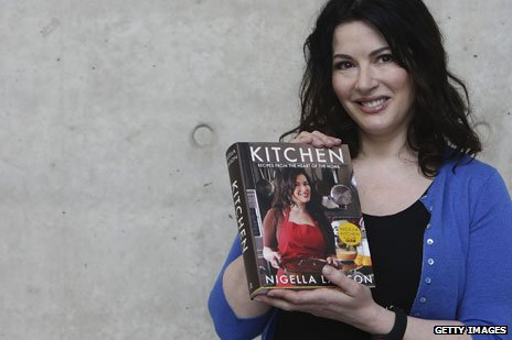 Nigella Lawson holding a copy of her 2011 book, Kitchen