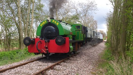 A steam train pulls wagons down the restored branch line.