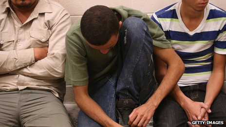 Male undocumented immigrants rest at the U.S. Border Patrol detainee processing center