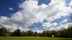 Clouds in a blue sky overlook a cricket match.