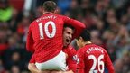 Robin van Persie of Manchester United celebrates scoring his second goal with Wayne Rooney and Shinji Kagawa