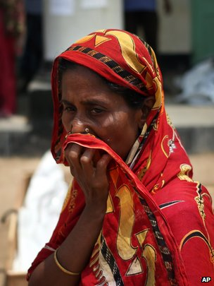 A woman covers her nose at a make-shift morgue in Savar, near Dhaka