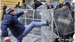 A man kicks at a policeman in Zagreb during demonstrations over high unemployment in Croatia