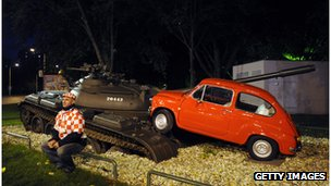 A museum display of a tank crushing a small car depicting a scene from Croatia's war of independence
