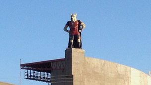 mascot on top of a football stadium