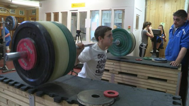 Alex Richardson (right) coaches a youngster in weightlifting