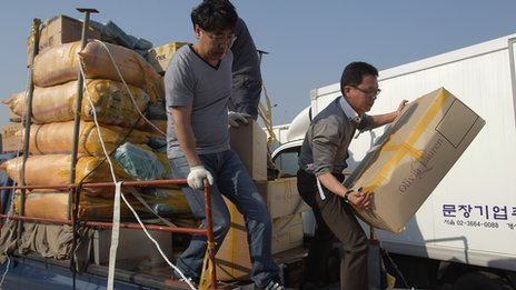 South Korean companies unload goods made in Kaesong across the border