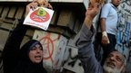 Egyptian protesters hold bread along with a flyer reading in Arabic 'Danger, no to loans that lead to poverty' during a rally in Cairo against the visit of a delegation from the International Monetary Fund on April 3, 2013