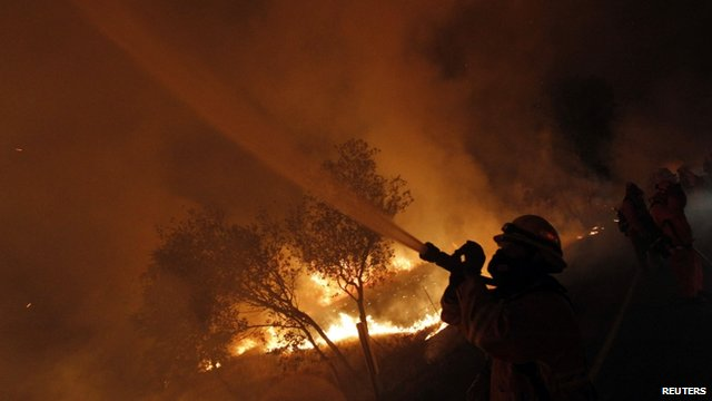 Firefighter hoses flames in California
