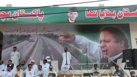 Signs decorating the stage at Sargodha rally