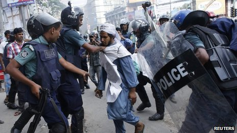 Police try to detain an activist during a clash in front of the national mosque in Dhaka, 5 May 2013