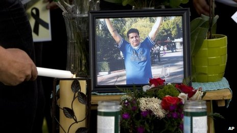 A mourner lights candles at a makeshift memorial for Ricardo Portillo