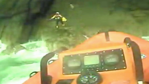 Two RNLI crewmen climb rocks