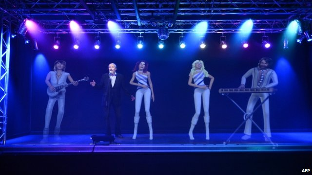 A man singing karaoke with a hologram featuring ABBA members