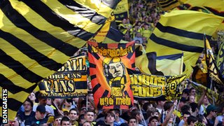 Dortmund fans waving flags during the recent game against Bayern Munich