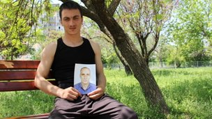 Txumir Arsenov holds up a picture of his father, who killed himself in protest