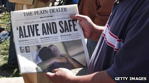 Man holds a copy of Cleveland Plain Dealer newspaper