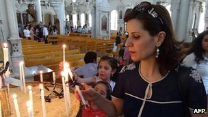Syrian Christians light candles before a mass marking the Palm Sunday on April 28 in Damascus