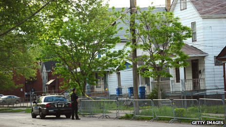A Cleveland police officer stands watch in front of the house on Seymour Street where three women were held captive for a decade