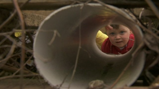 Boy looks down tube