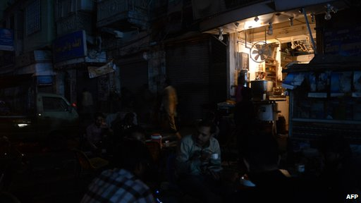 Pakistani people drinking tea outside a restaurant during a nationwide power blackout in Karachi