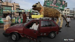 PML-N supporter with a model of a tiger on his car in Rawalpindi