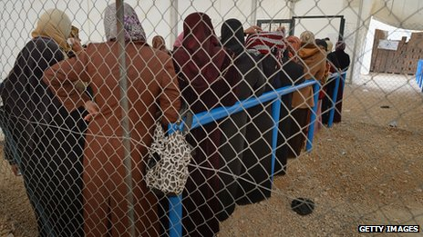 Syrian women collecting food and supplies from the UNHCR at Jordan's Zaatari refugee camp on 30 January 2013